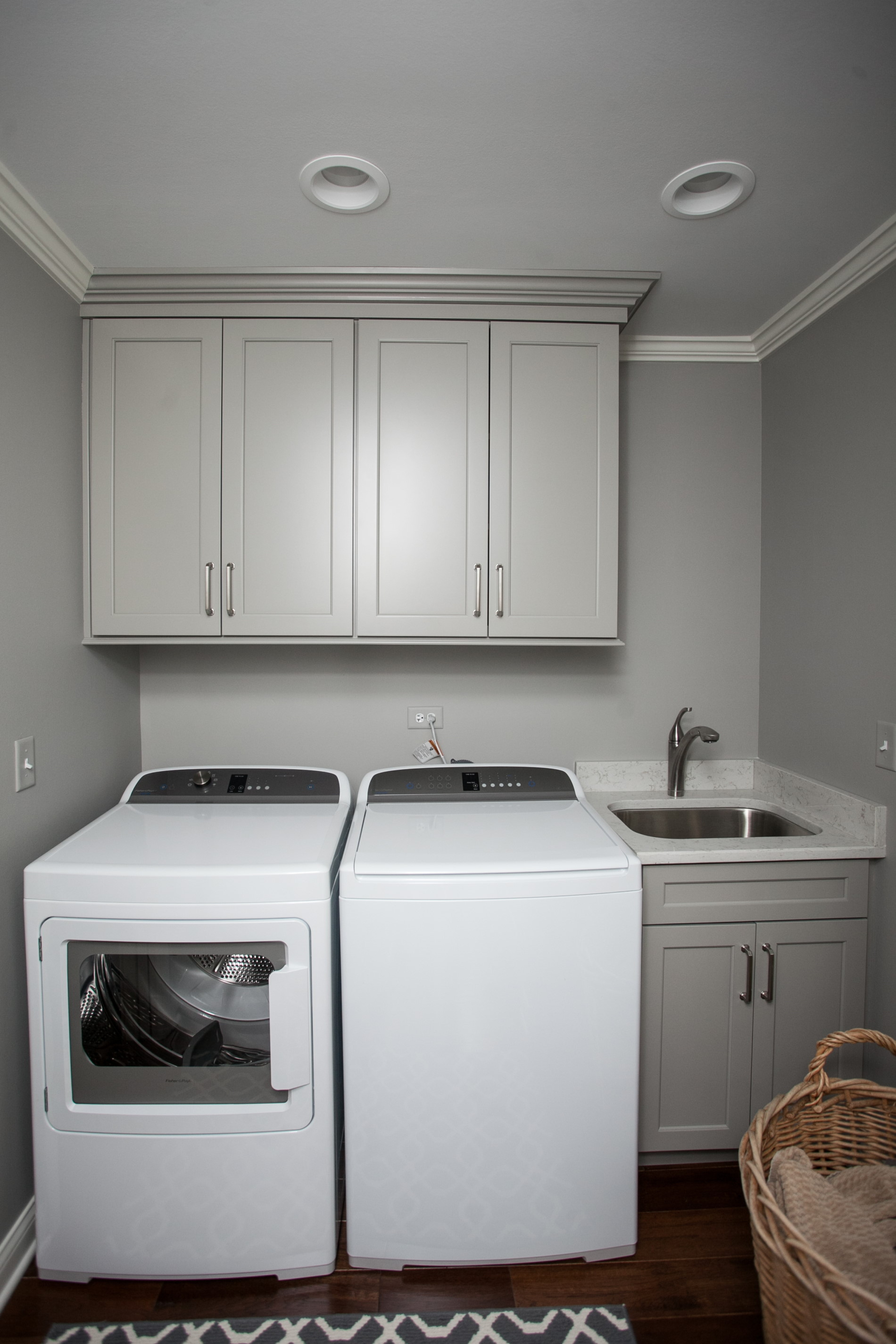 The laundry space was updated with a sink cabinet, and upper cabinets over the laundry machines.  The cabinets are our Amish custom cabinetry line in a painted finish.  The color is Benjamin Moore's Cape May Cobblestone.  A white quartz counter and undermount sink complete the utility sink area.