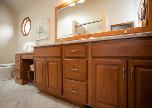 Beautiful double vanity with an abundance of storage;  and a petite vanity space with stool to primp at one's leisure.  The Custom Cupboards vanity is made of Alder wood with a spiced cider stain. 
