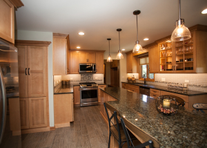 An overall tremendous improvement! The natural toned maple cabinetry keeps the kitchen lightened up but with rich accents.