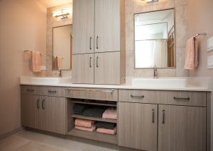 Contemporary laminate cabinetry creates a streamlined vanity. The soft grey and peach tones offer a soft and serene space in this hall bath.