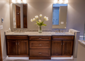 This beautiful cherry wood custom vanity is topped with MSI Quartz in Pacific Salt.  The toe kick lighting serves as a perfect night light.  And the floors are heated!  Is it a dream?