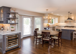 The expansive space is balanced in color and contrast.  The bar, which joins the family room and kitchen, is finished in Amish custom cabinetry in a grey stained finish and topped with Vadara Quartz. These same materials are repeated in the kitchen island.  The perimeter cabinets are a crisp white with black counters.