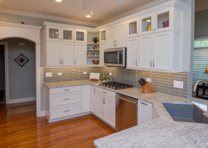 The glass doors in the upper cabinets are a perfect way to display special pieces.  The sink is an undermount Silgranit in grey, pairing beautifully with the Salinas White granite and polished taupe glass backsplash tile.