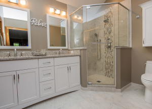 Double white vanity with undermount Kohler rectangular sinks makes this space easy to share.  Porcelain tile covers the floor, shower floor and walls but in varying sizes for interest.  The shower is accented with a porcelain mosaic vertical stripe.