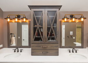 Beautiful tower cabinet with 'X' mullion doors.  It separates the two vanity spaces.  The cabinet is finished in a grey stain and sit atop iced white quartz.  The mirrors are framed in the same custom finish material and oil rubbed bronze fixtures complete the vanities, along with oil rubbed bronze hardware.