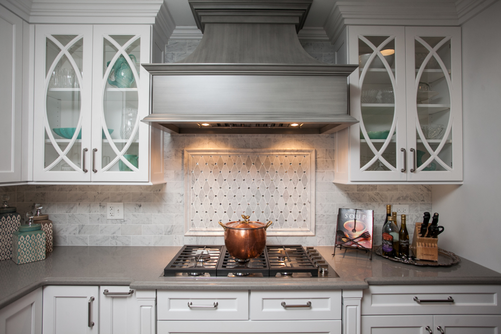 What a beautiful focal point in this kitchen.  A custom wooden hood with artistic finish, and custom mullioned glass doors.